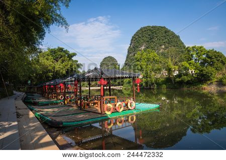 Scenic View Of Small Tourist Bamboo Rafts Sailing Along The Yulong River Among Green Woods And Karst
