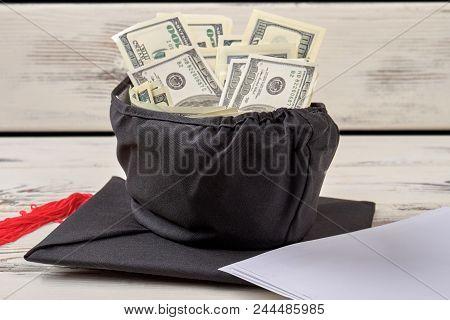 Bachelor Degree Hat Full Of Money. Black Bachelor Cap With Dollars.