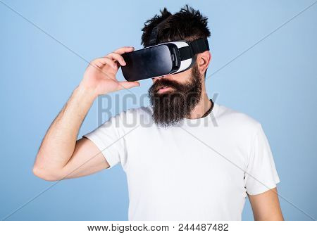 Man With Beard In Vr Glasses, Light Blue Background. Hipster On Serious Face Use Modern Gadget To Ex