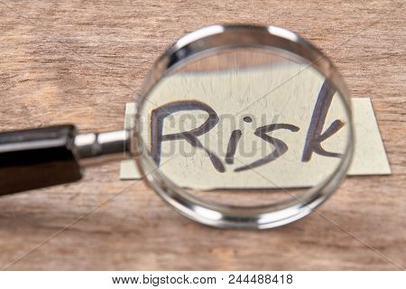 Magnifying Glass Zooming Risk Word, Close Up. Risk Concept. Wooden Desk Background.