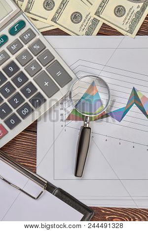 Finance And Statistic Concept. Magnifying Glass, Diagram Statistics, Calculator And Money Dollars.