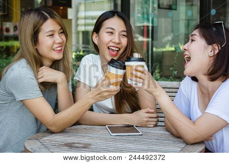 Cheerful Asian Young Women Sitting In Cafe Drinking Coffee With Friends And Talking Together. Attrac