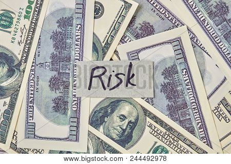 Money And Risk Concept. Pile Of Hundred Dollars And Risk Word.