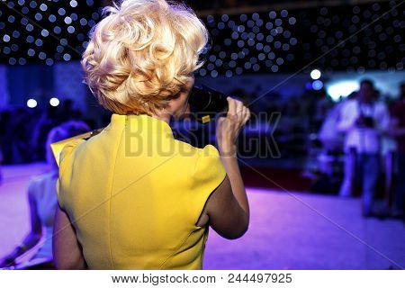 Back View Of Show Host Blonde Woman Holding Microphone Standing On Decorated Stage.