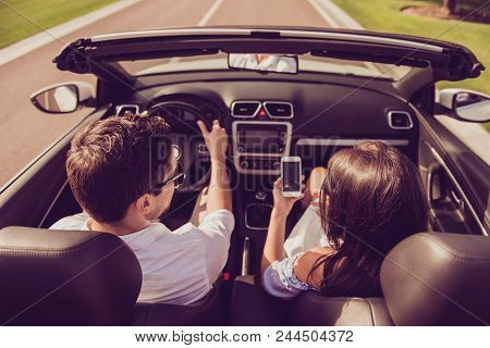 High Angle Shot Of Brunet Driver Husband, Brunette Lady Wife Show Him Screen Of Her Pda, On Their Wa