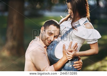 Parents, Love, Happiness, Maternity, Family Concept Happy Man Hugging Pregnant Wife