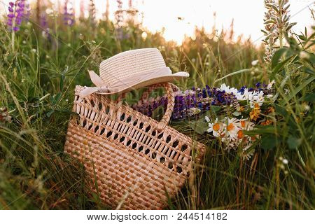 Vintage Straw Bag And Hat, Bouquet Of Wildflowers Chamomile In High Grass At Sunset Field.