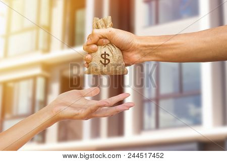 A Man Hand Holding A Money Giving To Another Person For Buying Real Estate. Loans For Real Estate Co