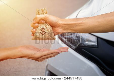A Man Hand Holding A Money Giving To Another Person For Buying New Car. Loans For New Car Concept. C
