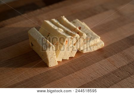 Six Sliced Cheese With Pieces Of Paprika On Wooden Bamboo Cutting Board At Home Kitchen In Morning