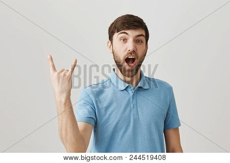 Positive Good-looking European Male Showing Rock Gesture And Shouting, Being Upbeat And Excited With