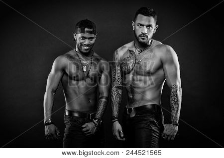 Machos With Muscular Tattooed Torsos Look Attractive, Dark Background. Athletes On Confident Faces W