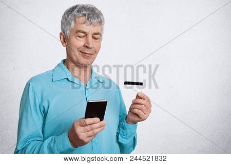 Elegant Male Pensioner Holds Smart Phone And Credit Card, Checks His Account And Pension In Online W