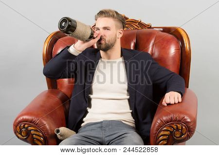 Businessman Formal Suit Sit Leather Chair, Grey Background. Man Serious Face Relaxing With Alcohol I