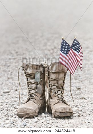 Old Military Combat Boots With Dog Tags And Two Small American Flags. Rocky Gravel Background With C