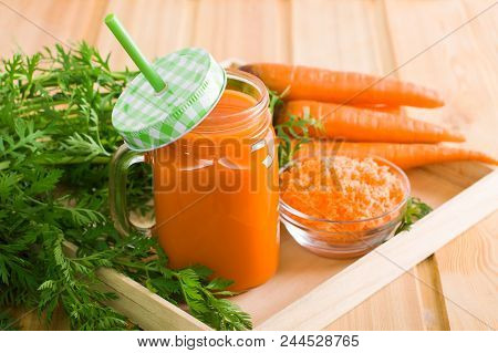 Mason Jar With Fresh Carrot Juice And Green Straw, Bunch Of Carrot With Green, Glass Cup Of Squeezed