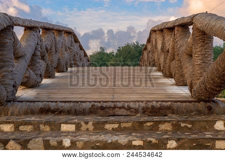 Wooden Bridge Made Of Palm Trunks Leading To Trees With Partly Cloudy Sky In Sunrise Time At Montaza
