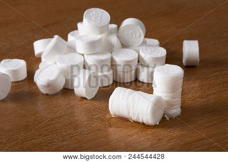 A Heap Of Compressed Coin Tissues And Expanded Tissue After Wet, On A Wooden Background