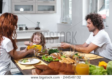 Cheerful Girl Is Eating Healthy Food Together With Her Parents. She Is Taking Salad From Bowl And Sm