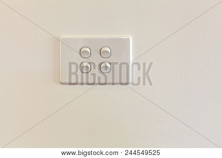 Quad Modern Light Switch On White Wall With Copy Space