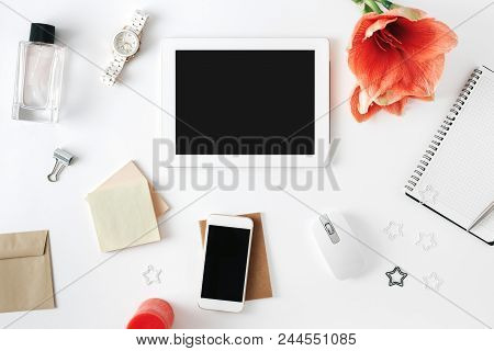 Flat Lay, Top View Office Table Desk. Feminine Desk Workspace With Flower Amaryllis, Tablet, Noteboo