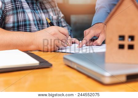 Real Estate Agent Showing His Client Where He Has To Sign A Contract On Sealing Deal.