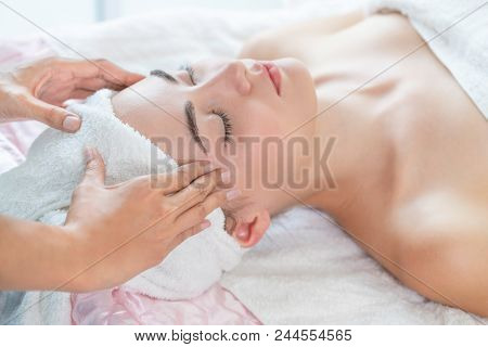 Woman Gets Facial And Head Massage In Luxury Spa.