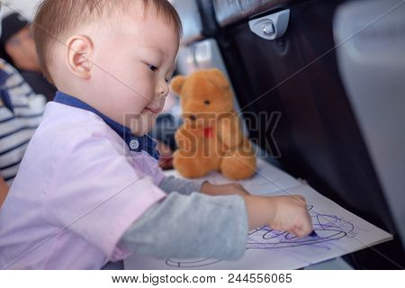 Little Asian 1 Year Old Toddler Boy Coloring In Coloring Book With Crayons During Flight On Airplane