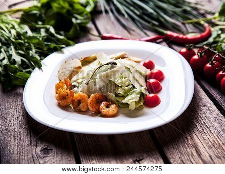 Salad With Meat, Cheese And Tomatoes On A Wooden Background A