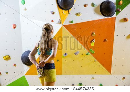 Young Woman Putting Chalk On Hands And Looking At Bouldering Problem She Is Going To Climb. In Indoo