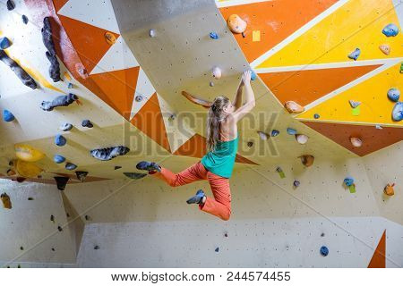 Young Athletic Woman Jumping On Handhold In Bouldering Gym
