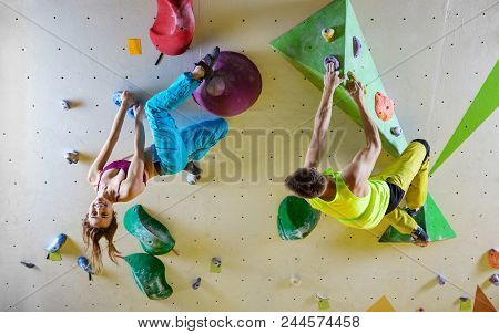 Rock Climbers In Bouldering Gym Climbing Up Overhanging Wall. Young Woman Hanging Upside Down And Sm