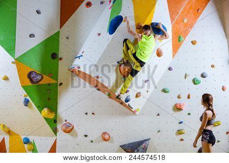 Rock Climbers In Climbing Gym. Young Man Climbing Bouldering Problem (route), Girl Climber Watching