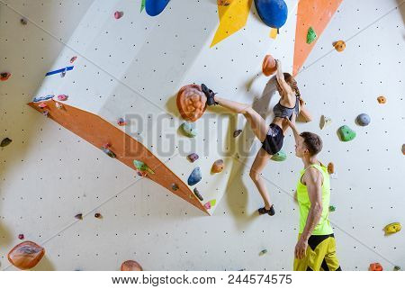 Rock Climbers In Climbing Gym. Young Woman Climbing Bouldering Problem (route), Male Instructor Secu