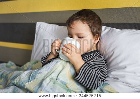 Sad Ill Curing Boy Sitting On Bed On Pillow Under Blanket Drinking Medicine In Cup