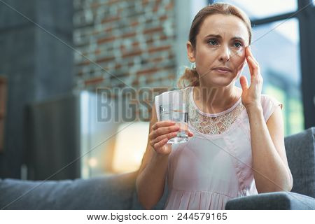 Migraine Triggers. Low Angle Of Pleasant Mature Woman Posing On Blurred Background While Carrying Gl