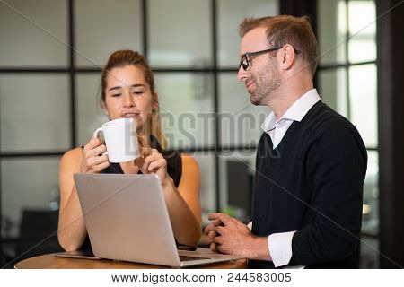 Relaxed Business Partners Chatting And Working At Cafe Table. Woman Holding Cup And Man Using Laptop