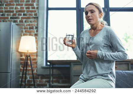 Cold Sweat. Low Angle Of Beautiful Mature Woman Sweating And Carrying Glass Of Water