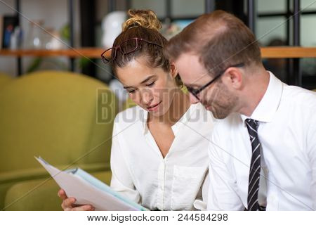 Serious Coworkers Discussing Document In Office Lobby. Business Man And Woman Sitting On Couch And H