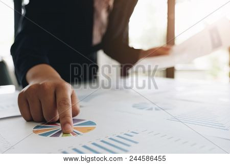 Close Up Of Business Man Hand Pointing At Business Document With Financial Statistics At Office Work