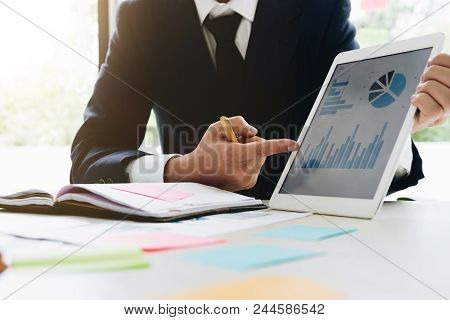 Image Of An Office Worker Using A Touchpad To Analyze Statistical Data - Business Present Financial