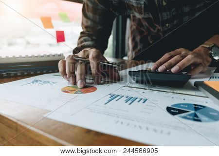 Man Calculating Individual Income Tax From Financial Document With Calculator At His Office - Busine