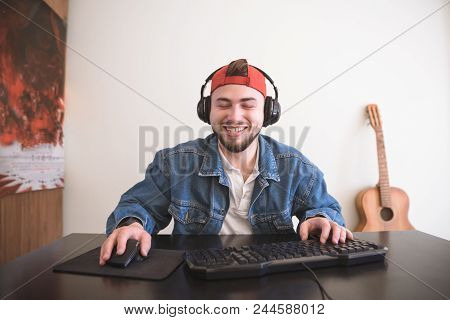 Happy Adult Gamer With Beard Playing Video Games At Home With A Computer. Smiling Man With A Beard S