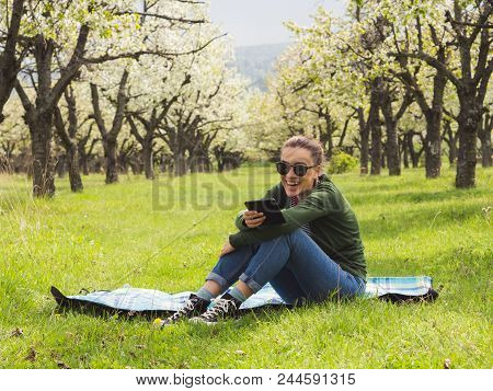 Young Attractive Woman Reading On Her Ebook Outdoors And Laughing. Beautiful Blooming Cherry Trees I