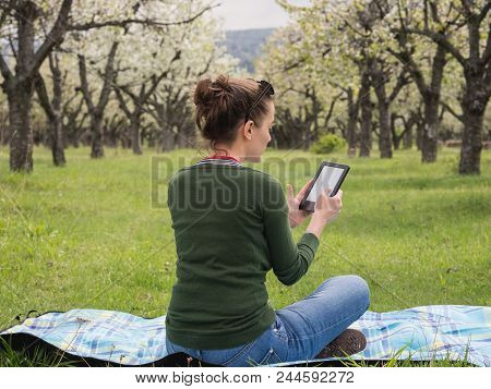 Rear View Of A Young Woman Outdoors Reading On Her Ebook. Beautiful Blooming Cherry Trees In The Bac