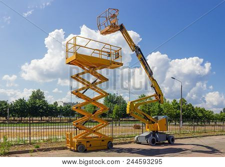 Yellow Self Propelled Articulated Boom Lift And Scissor Lift On Background Of Street With Trees And