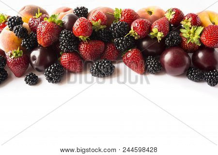 Black And Red Food At Border Of Image With Copy Space For Text. Ripe Blackberries, Strawberries, Plu