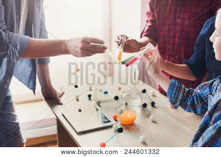 Pupils with teacher doing biochemistry research in chemistry class, using laboratory tubes with colorful liquids. Stem education. Early development, education, diy, innovation concept. poster