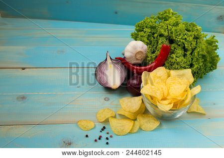 Crispy Potato Chips In A Glass Bowl With Chili Peper, Garlic, Salad  And Onions On Old Blue Wooden B