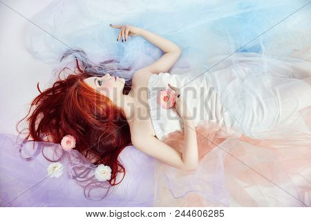 Redhead Girl In Light Airy Colored Dress Lies On The Floor White Background. Beautiful Flowers In Gi
